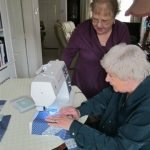 Eileen giving Freda 'one-to-one' instruction on machine sewing